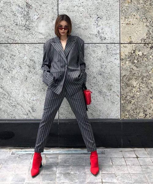 MLee đột phá với cây vest xám đậm chất menswear, dùng túi xách và boots đỏ làm điểm nhấn.