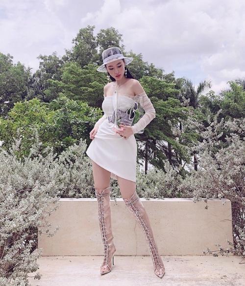 Angela Phương Trinh bắt kịp xu hướng phụ kiện nhựa trong suốt bằng cách phối boots cao cổ dây đan cùng mũ bucket và túi xách mini.