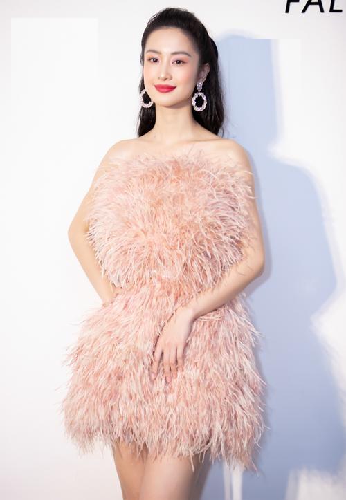 Jun Vũ thanh thoát, ngọt ngào nhưng không kém phần gợi cảm khi chọn chiếc váy cúp ngực được thực hiện trên nền chất liệu lông mềm mại. Sắc hồng pastel trở thành điểm nhấn thú vị giữa rừng sắc hồng sậm rực rỡ. Cô phối hoa tai to bản, đi gày có thiết kế cổ điển, cùng tông trang phục.