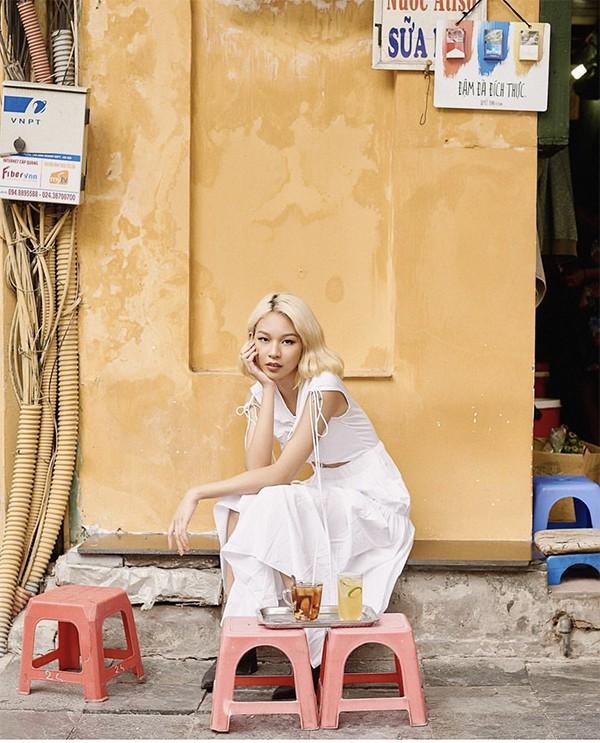 Với mục đích tôn mái tóc vàng mới nhuộm để đón Tết, Phí Phương Anh đã chọn mẫu váy trắng trang trí dây rút bắt mắt. Trang phục đi chơi xuân của cô khác hẳn sự nổi loạn và phá cách thường ngày.
