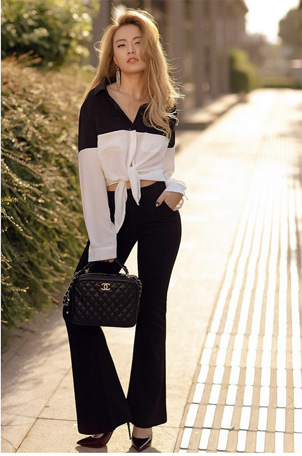 Tông màu trắng đen được Hoàng Thuỳ Linh phối hợp một cách nhịp nhàng từ sơ mi, quần loe cho đến túi Chanel và giày cao gót.