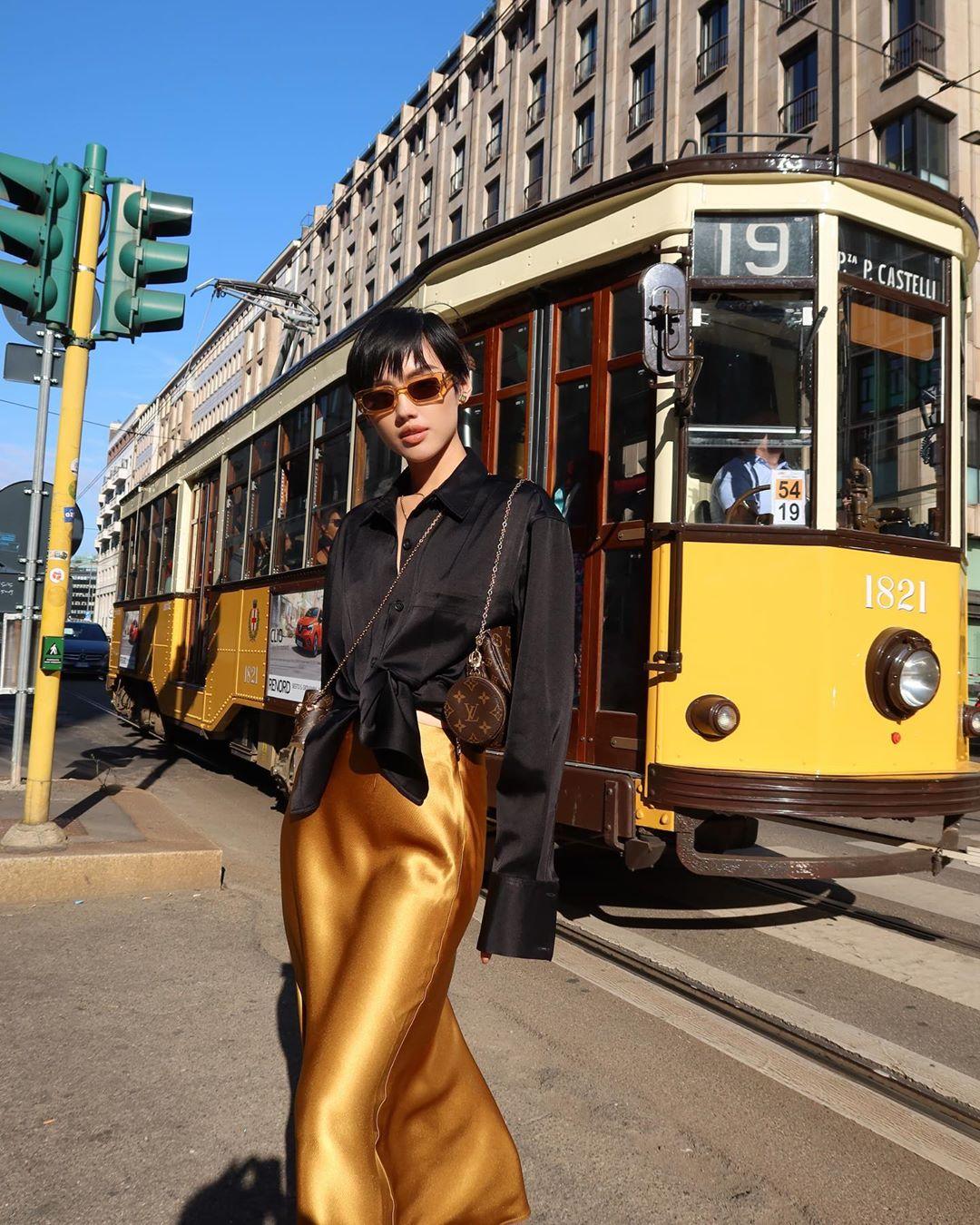khánh linh mặc chân váy vải lụa vàng áo sơ mi đen