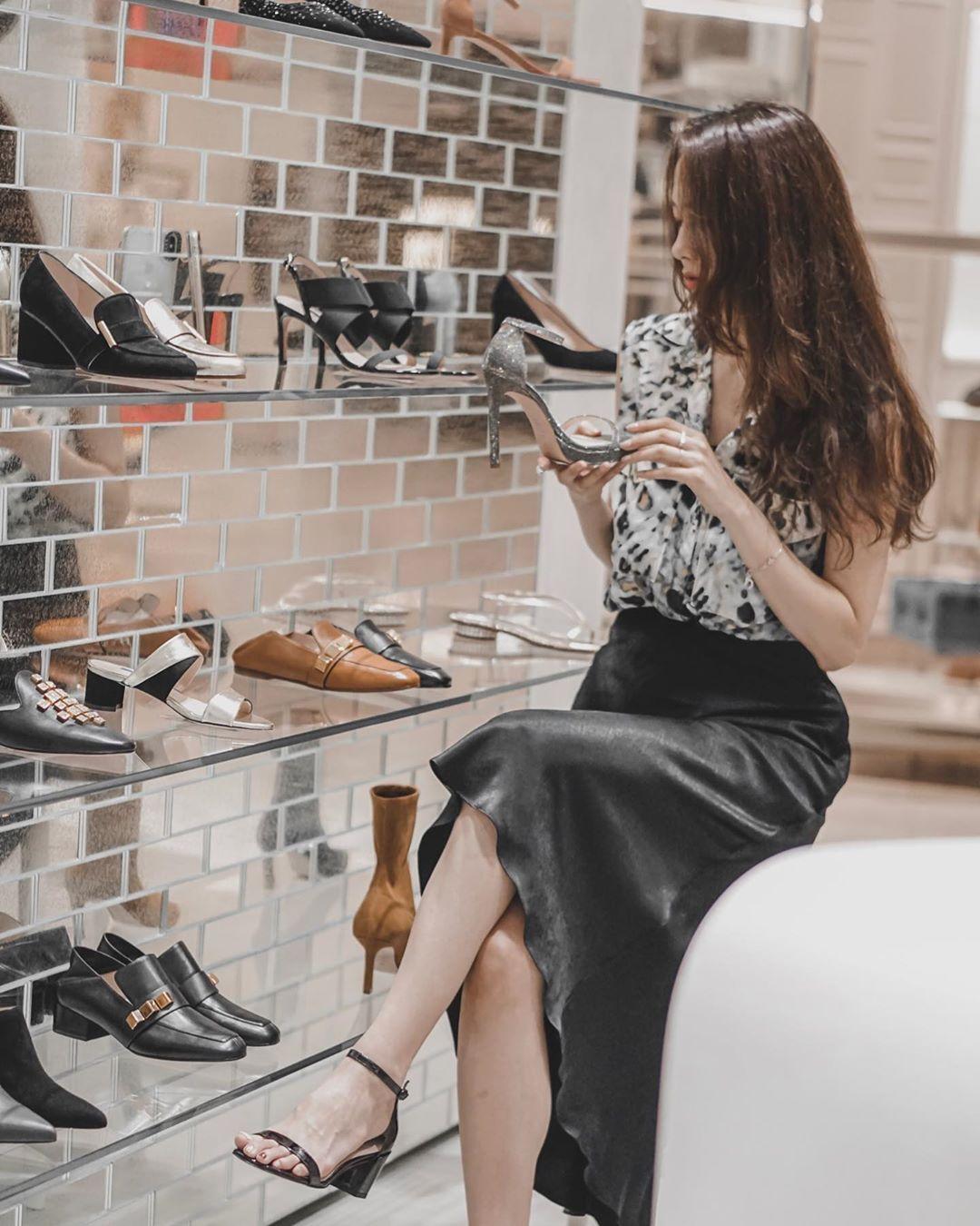 ms gabby mặc chân váy vải lụa màu đen và áo voan ngắn tay