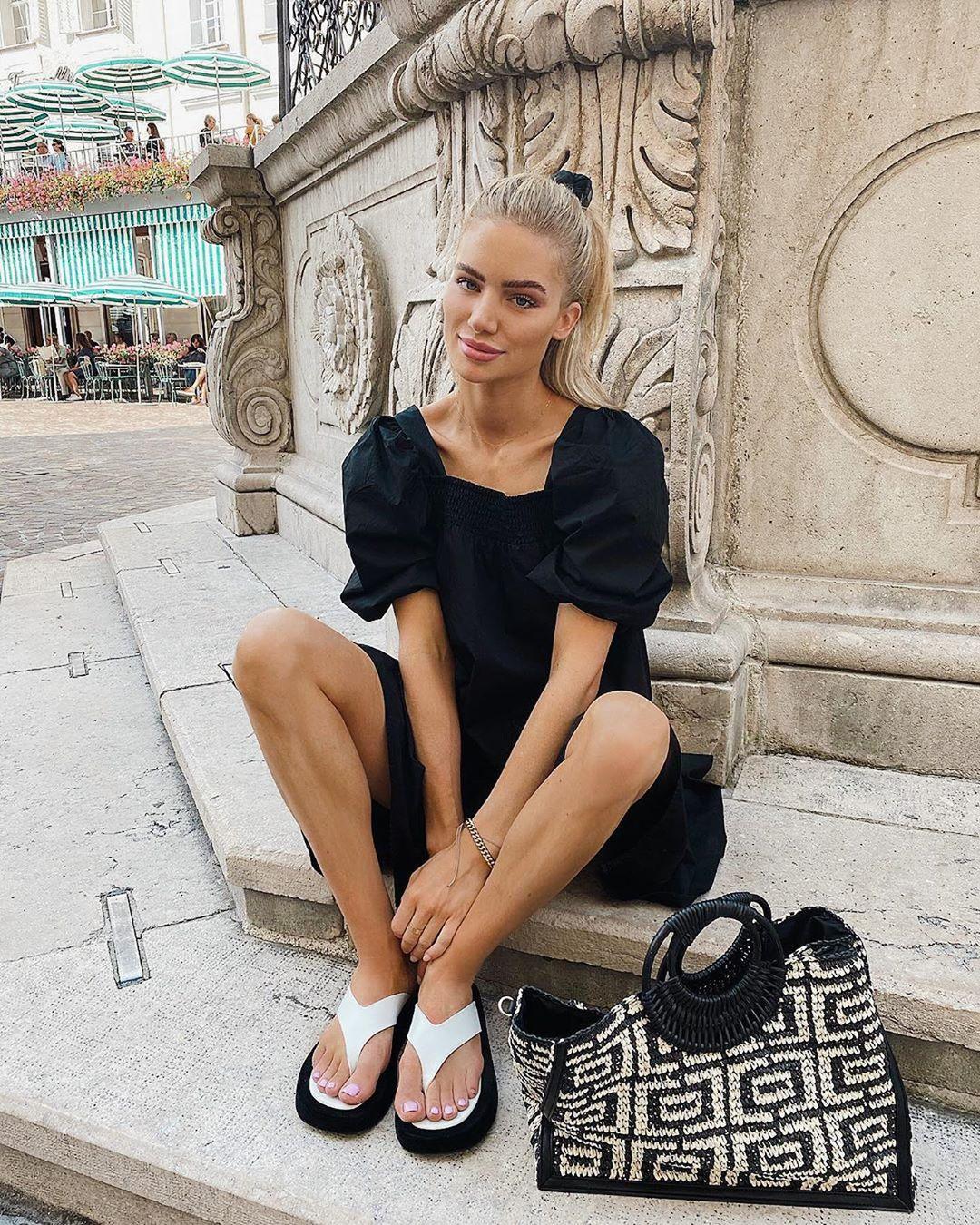 Cô gái mặc váy đen mang dép nữ xỏ ngón màu trắng