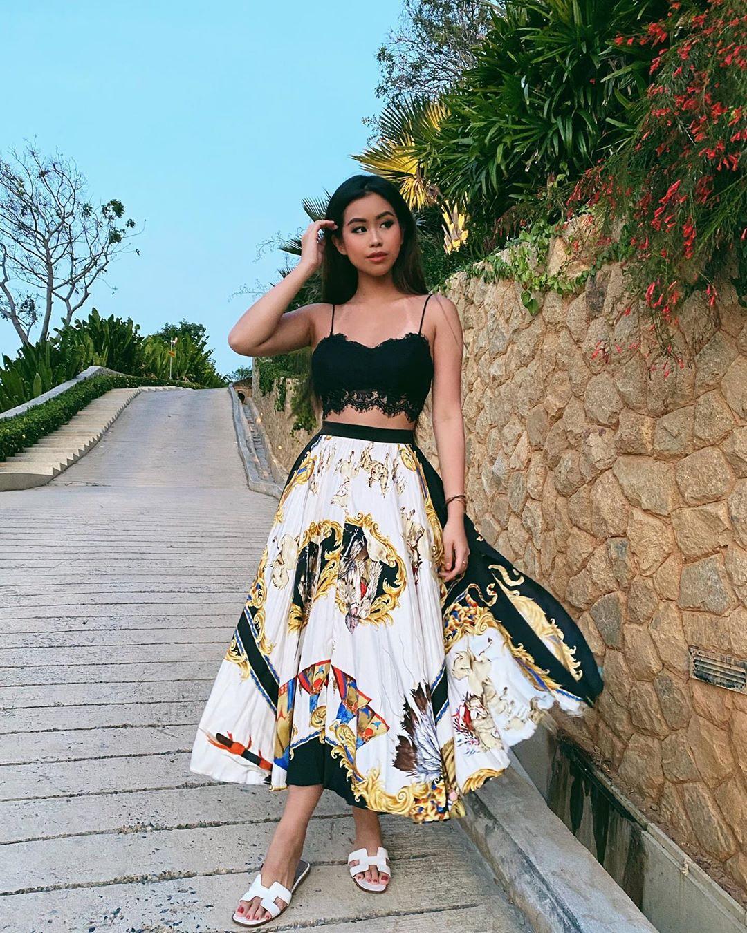 Tiên Nguyễn mặc váy xòe, mang dép nữ màu trắng