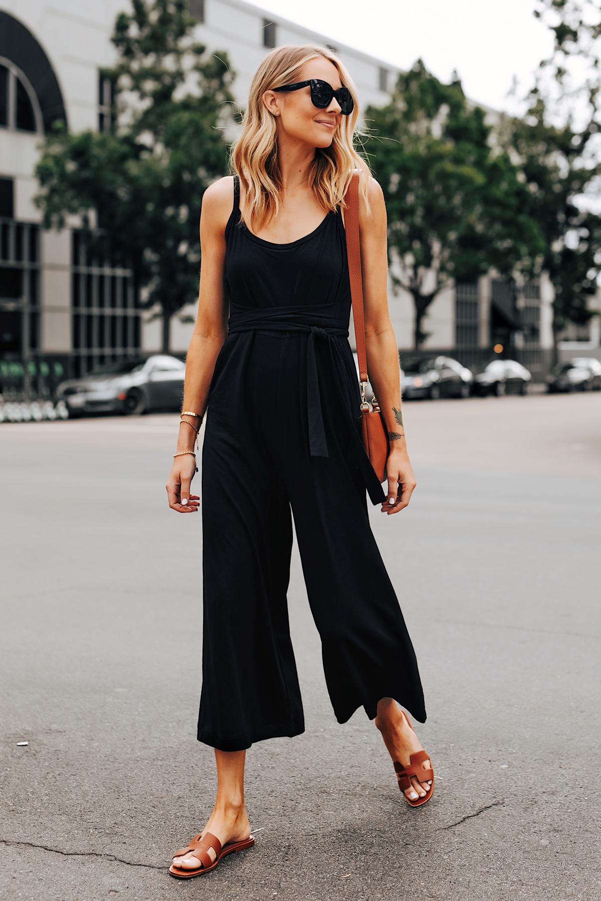Cô gái mặc jumpsuit đen, mang dép nữ quai ngang màu nâu
