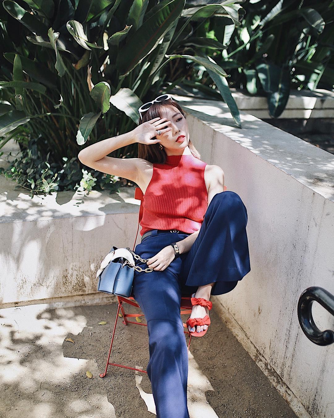 Cô gái mặc áo đỏ, quần xanh, mang dép nữ màu đỏ